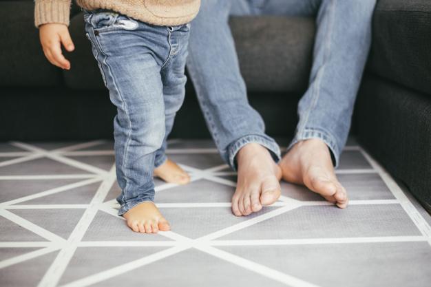 pies de padre e hijo sobre alfombra en casa